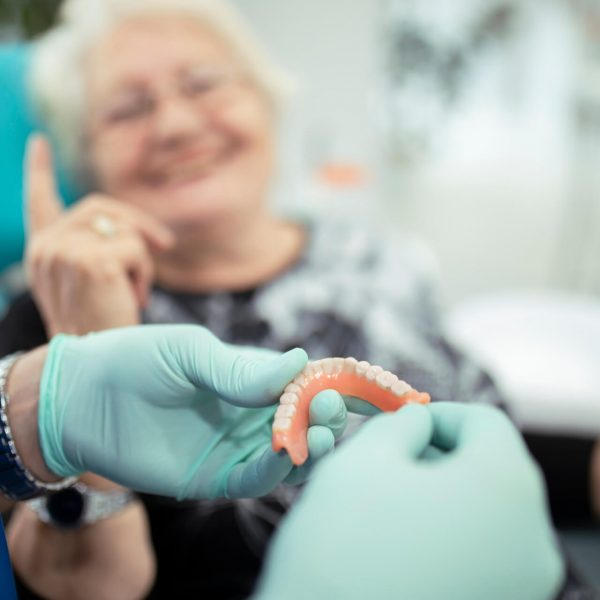 image-dentist-showing-teeth-dentures-to-a-patient